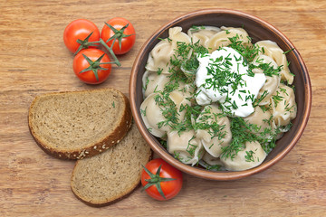 dumplings with fresh herbs and sour cream in a dish, cherry toma