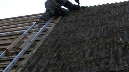 A roofer climbing on to the ladder