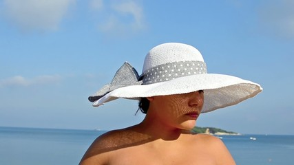 Girl with straw hat yawning in the beach