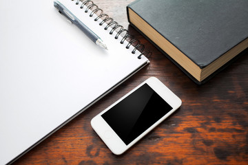 Blank notebook and mobile phone on wood table