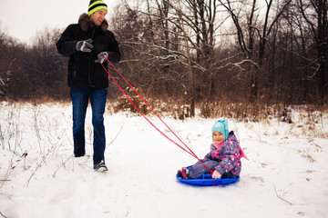 Image of adult pulling daughter on a sled (concept: winter fun)