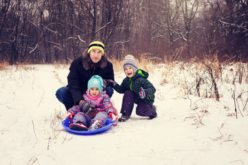 Image of adult with two children on a sled