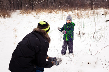 Portrait of a boy playing with father outdoors in the snow