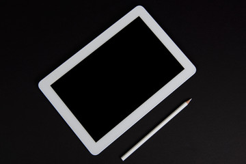 Touchpad with white pencil on a black table
