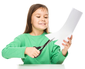 Little girl is cutting paper using scissors