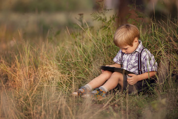 Child with tablet pc outdoors.