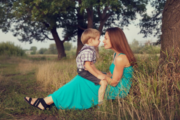 mother and son sitting face to face in countryside
