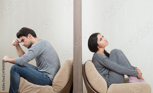 Conflict between man and woman sitting on either side of a wall - 74840986
