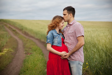 pregnant woman and her husband walking in the countryside