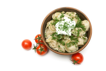dumplings with fresh herbs and sour cream in a clay plate and to