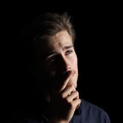 Attractive man thinking on black