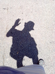 Wave of a hand in greeting. Shadow on the pavement