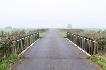 Bridge over water in a misty morning rural landscape in the Neth