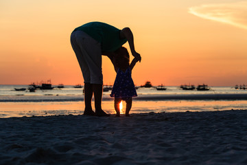 Silhouette of father and little daughter on sunset