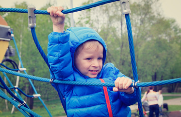 little boy climbing rope on the playground