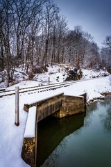Snow covered railroad bridge over a creek in rural Carroll Count