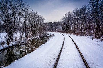 Snow covered railroad tracks and creek in rural Carroll County,