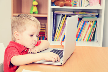 little boy working on laptop at home