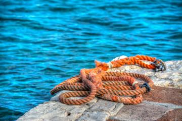 orange rope on a rocky pier