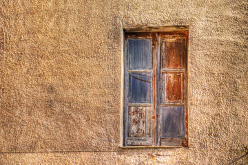 wooden window in a yellow rustic wall