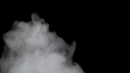 Smoke billowing over a black background. 4K UHD 2160p footage.
