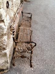 vieux banc rouillé contre un mur