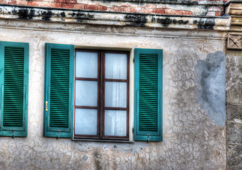 green shutters in a rustic wall