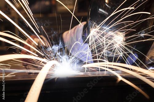 Zdjęcia na płótnie, fototapety, obrazy : Employee welding steel using MIG/MAG welder.