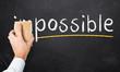Hand wischt mit Schwamm das 'im' von 'impossible' weg