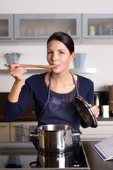 Junge Frau probiert beim Kochen in der Küche