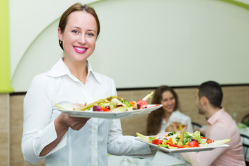 Waitress serving food to visitors