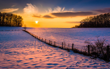 Sunset over a fence in a snow covered farm field in rural Carrol