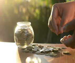 Male hands putting money coins into piggy bank