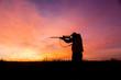 Leinwandbild Motiv Rifle hunter Silhouetted at Sunrise