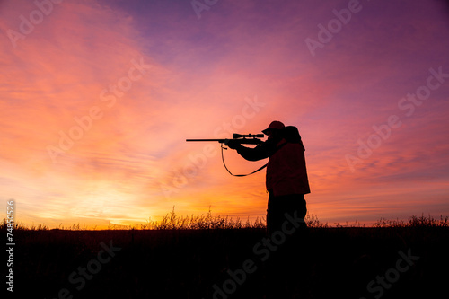 Rifle hunter Silhouetted at Sunrise - 74850526
