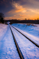 Sunset over snow-covered railroad tracks in Carroll County, Mary