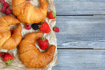 French croissant with berries on paper