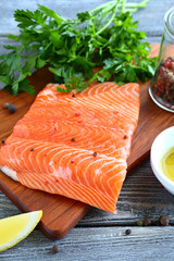 Salmon with greens and lemon on a board