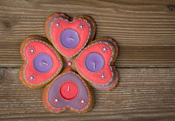 Gingerbread hearts with candles on wooden background