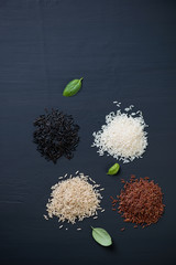 Red, brown, white and black rice over black wooden background
