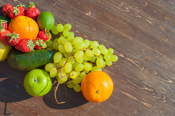 Colorful fruits on brown wood in natural light