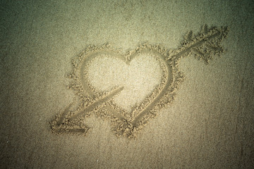 Heart drawn in the sand. Beach background. Top view. Tinted