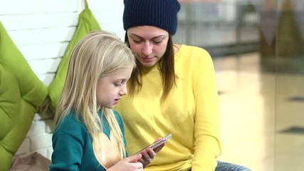 Little girl and her mother playing with smart phone