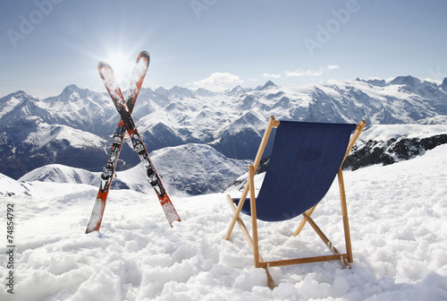 Papiers peints Glisse hiver Cross ski and Empty sun-lounger at mountains