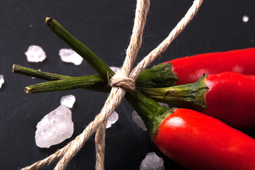 three related twine red hot peppers on a blackboard tinted