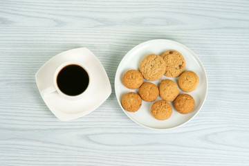 Coffee cup with oatmeal cookies on the white plate