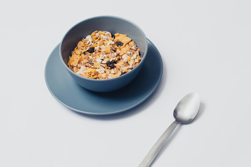 Muesli in a bowl and spoon. White background.