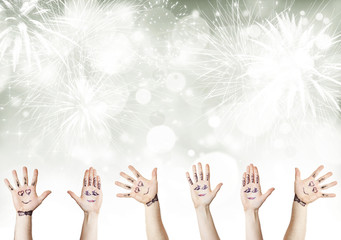 Painted palms with smiling faces celebrating New Year
