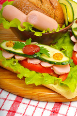 Big appetizing fast food baguette sandwich with lettuce, tomato