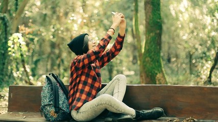 Hipster girl using smartphone in the forest